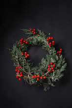 Christmas Wreath Detail Of Evergreen And Berries On Dark Background.
