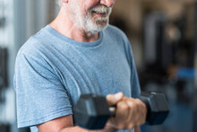 Adult Man And Mature Senior At The Gym Working His Body With Dumbbell - One Man Hapy Training Indoors