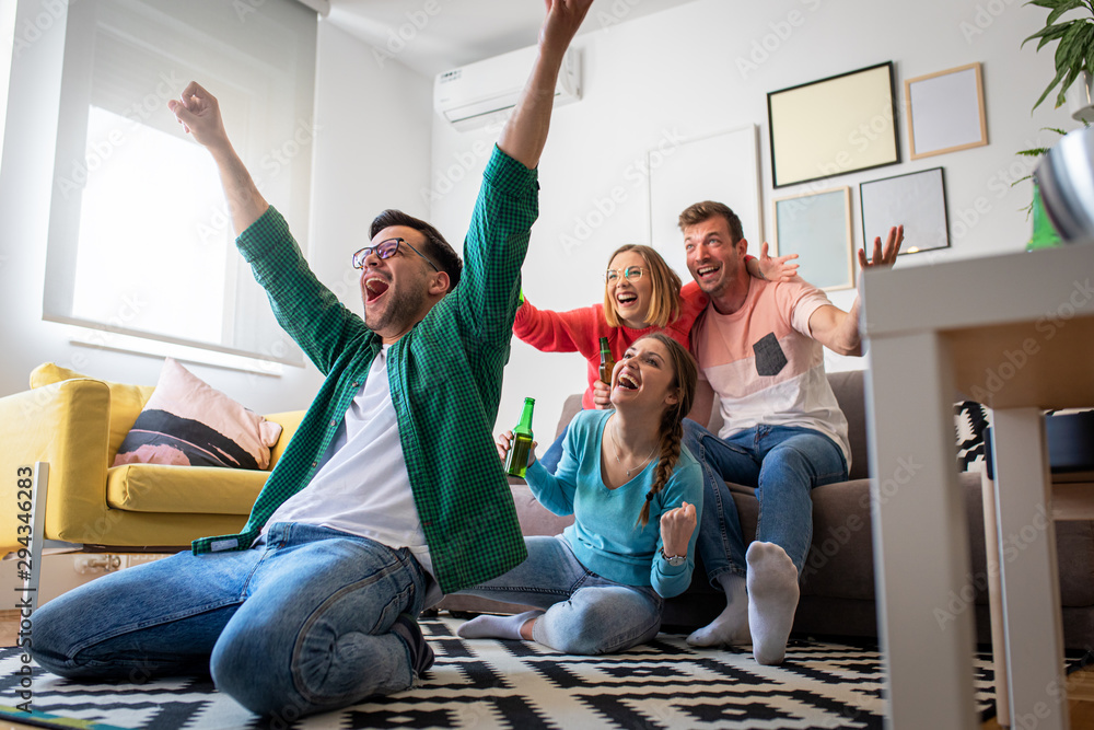 Fototapeta Group of cheerful friends watching soccer match and celebrating victory at home. Man on his knees cheering for his team.