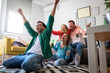 canvas print picture - Group of cheerful friends watching soccer match and celebrating victory at home. Man on his knees cheering for his team.