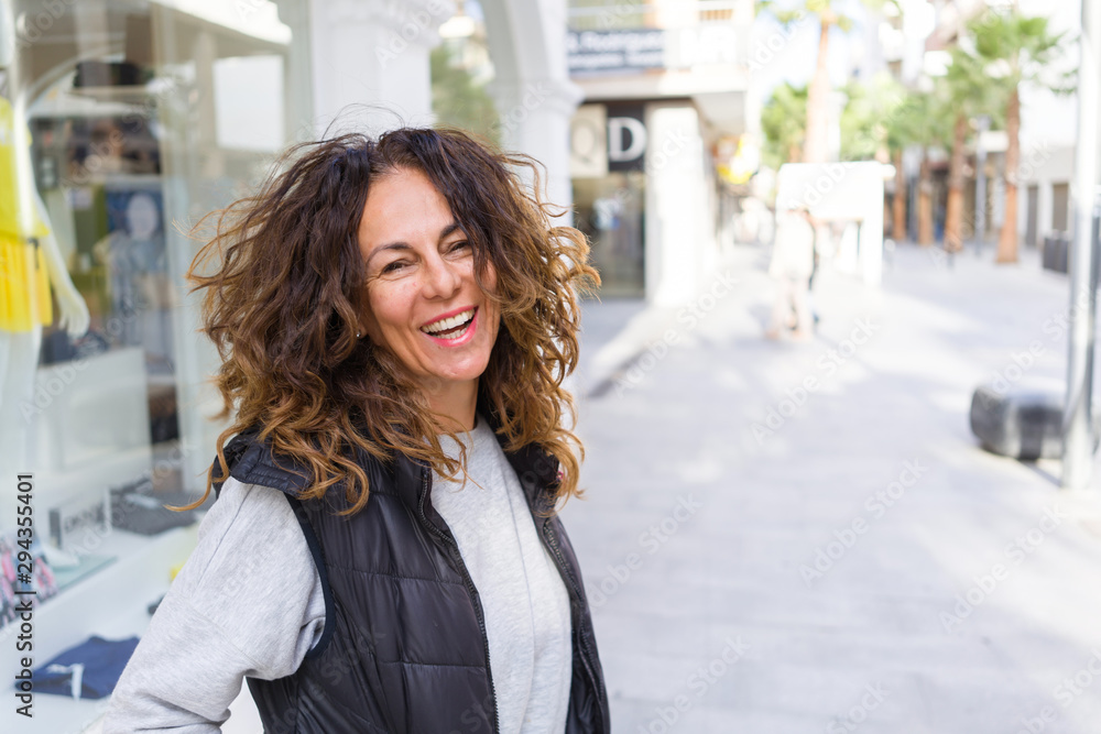 Fototapeta Beautiful sporty woman with curly hair smiling cheerful walking on the streets at the town