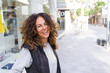Beautiful sporty woman with curly hair smiling cheerful walking on the streets at the town