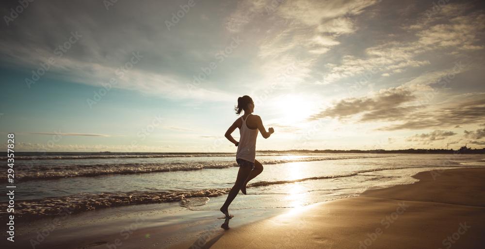 Fototapety, obrazy: Fitness woman runner running on sunset beach