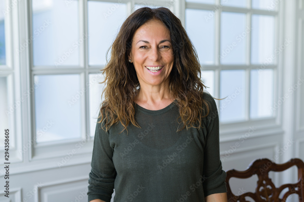 Fototapeta Beautiful middle age woman at home smiling cheerful
