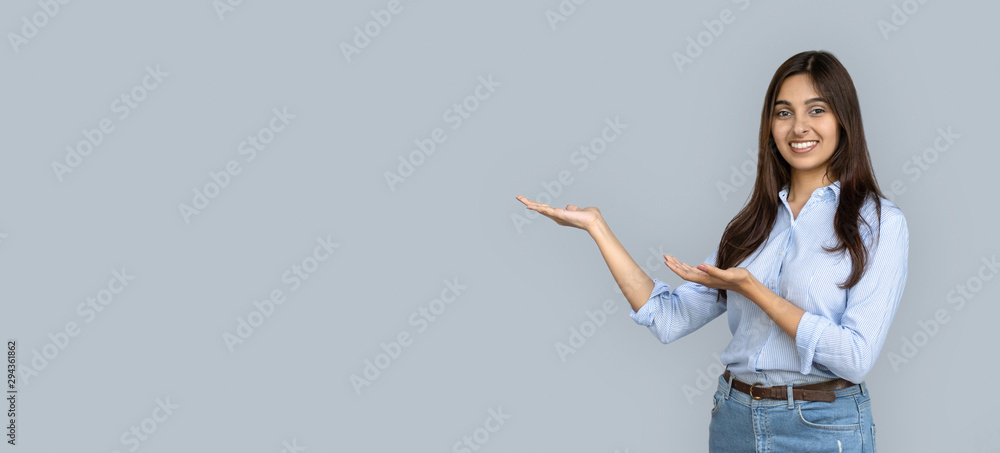 Fototapety, obrazy: Smiling young adult indian woman stand isolated on grey background holding copy space on hands pointing. Happy girl student professional looking at camera advertise product service concept, banner