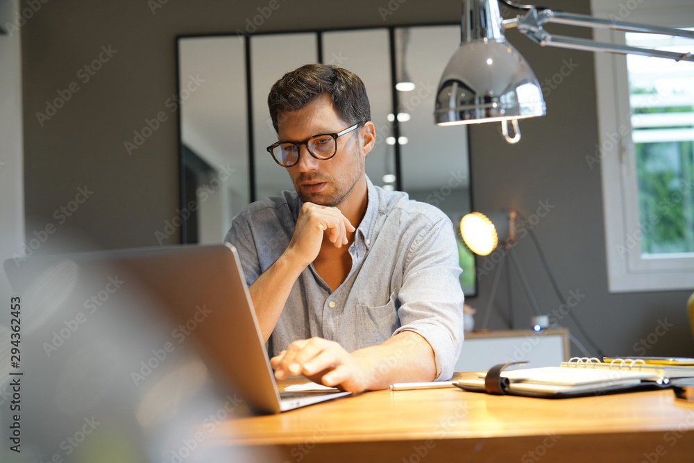 Fototapeta Middle-aged man working on laptop in office