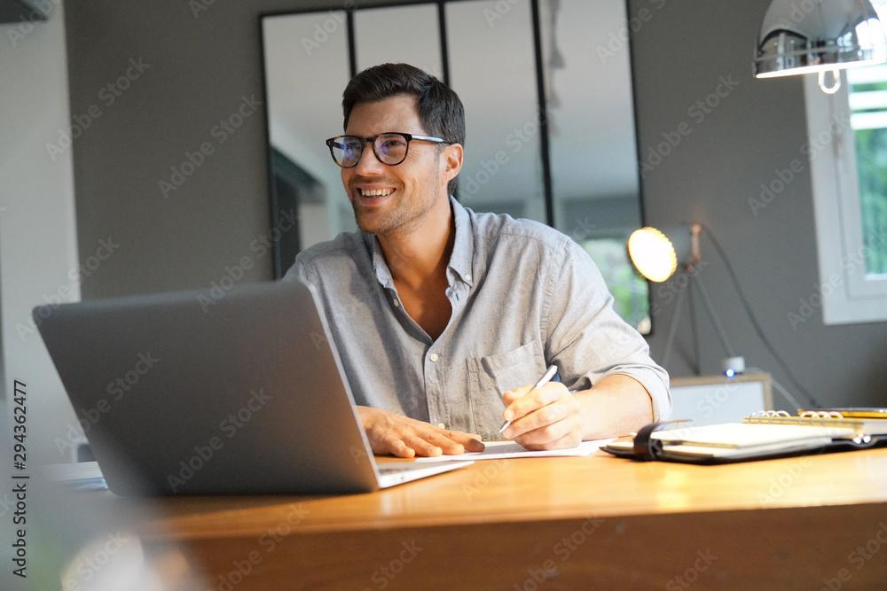 Fototapeta smiling man working in an office.