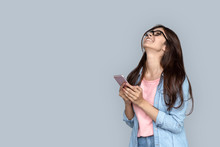 Overjoyed Excited Young Adult Indian Woman Standing Isolated On Grey Background With Copy Space. Euphoric  Girl Student Holding Modern Smartphone Celebrating Mobile Win Victory Social Media Success