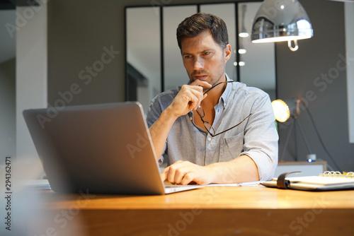 Fototapeta Middle-aged man working on laptop in office obraz na płótnie