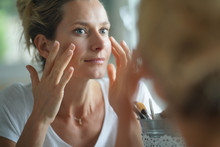 Portrait Of Woman Looking At Her Face In Mirror
