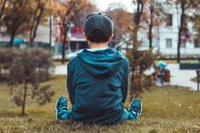 Boy Sitting On The Grass Wearing Blue Hoody, Jeans, Black Snapback And Sneakers In The Autumn Park. Seasons And Loneliness Concept.