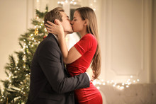 Passionate Couple Kissing In Front Of  The Christmas' Tree In Their Home