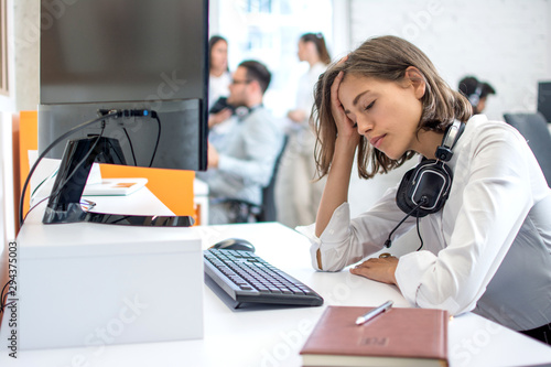 Photo  Young attractive woman operator with headset over neck suffering from headache