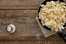 Top View Of Fresh Popcorn In Frying Pan With Salt On Wooden Background