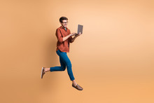 Full Length Body Size View Of His He Nice Attractive Cheerful Cheery Glad Brunet Guy Jumping In Air Using Laptop Part-time Job Isolated Over Beige Color Pastel Background