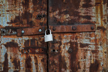 The Old Iron Gate Is Closed On A New Padlock. The Doors Are Rusted. Visible Bolt Heads - Rusty And Silver. Background. Texture.