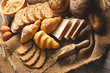 Leinwandbild Motiv Different kinds of bread with nutrition whole grains on wooden background. Food and bakery in kitchen concept. Delicious breakfast gouemet and meal. Top view angle