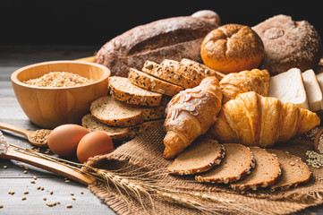 Različite vrste kruha s hranjivim cjelovitim žitaricama na drvenoj podlozi. Hrana i pekara u kuhinjskom konceptu. Ukusan doručak gouemet i obrok.