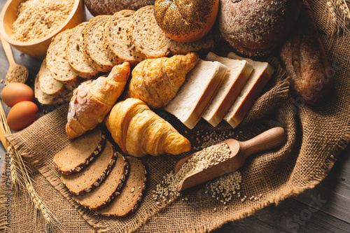 Fototapeta Different kinds of bread with nutrition whole grains on wooden background. Food and bakery in kitchen concept. Delicious breakfast gouemet and meal. Top view angle obraz