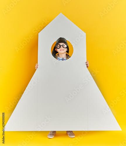 Smiling boy holding a big toy rocket Canvas Print