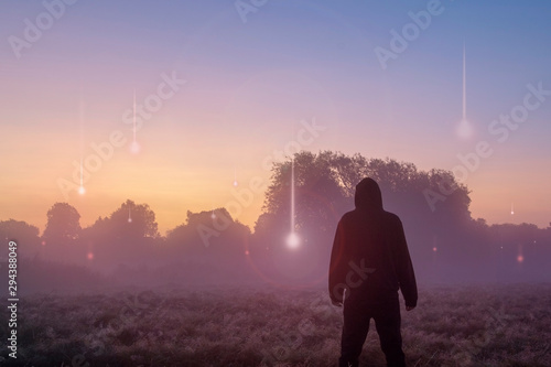 Türaufkleber UFO A UFO, supernatural concept. A hooded figure with his back to the camera, looking at lights falling from the sky. Across a misty field at sunrise.