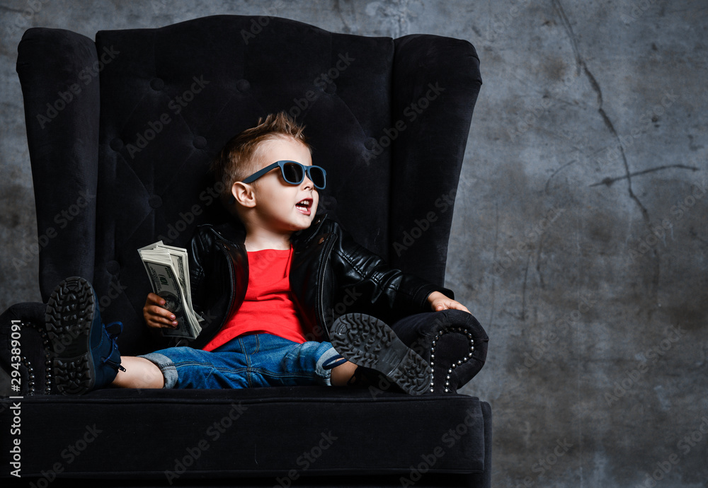 Fototapeta Rich kid boy in sunglasses and leather jacket is sitting in big luxury plush armchair with a stack of money talking