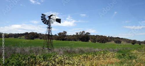 Rusty old solitary windmill in a  country field