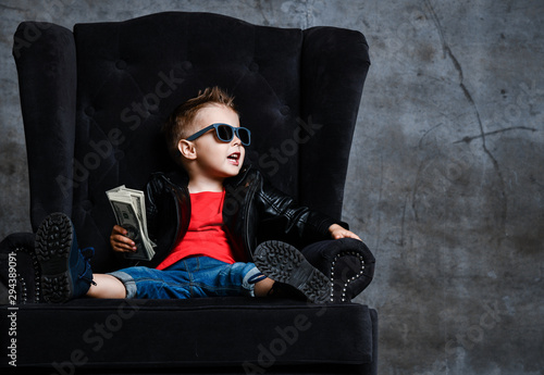 Fototapeta Rich kid boy in sunglasses and leather jacket is sitting in big luxury plush armchair with a stack of money talking obraz