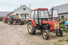 Red Tractors And Agricultural Equipment In The Courtyard Of A Dairy Farm. A Cowshed In The Background.Close Up. Podlasie, Poland.