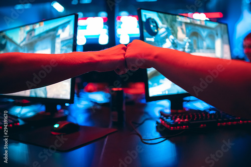 Fotografie, Obraz Professional gamer greeting and support team fists hands online game in neon color blur background