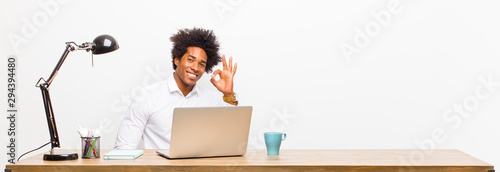 Photo young black businessman feeling happy, relaxed and satisfied, showing approval w