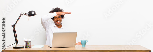 young black businessman smiling, feeling happy, positive and satisfied, holding or showing object or concept on copy space on a desk - 294394666
