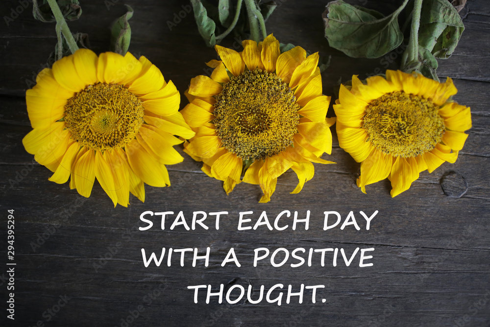 Fototapeta Inspirational motivational quote - Start each day with a positive thought. With yellow sun flowers on rustic wooden table background. Words of wisdom concept.