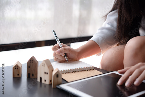 wooden toy house medel with Woman Plan to sign a contract to buy a house, Real estate concept Canvas Print