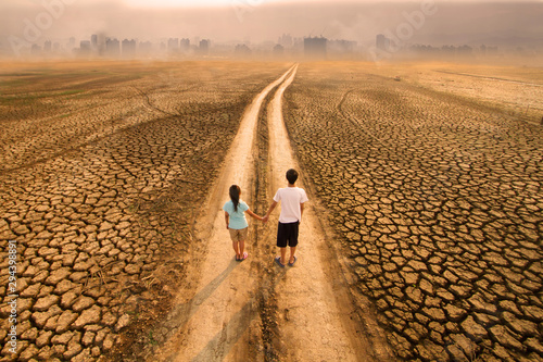Climate change and Environmental Pollution, Drought impact to river and lake around the city with two children standing on dirty road Fototapet