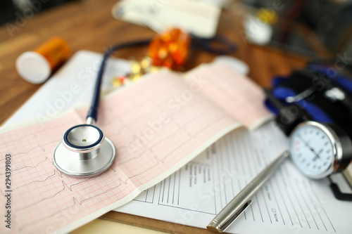 Empty GP office with stethoscope head lying at cardiogram paper Canvas Print