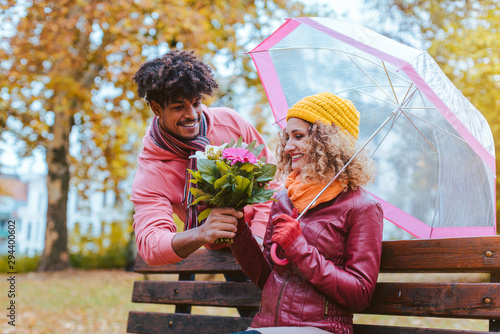 Fototapeta Man surprising his wife with a bouquet of flowers on a drizzly fall day