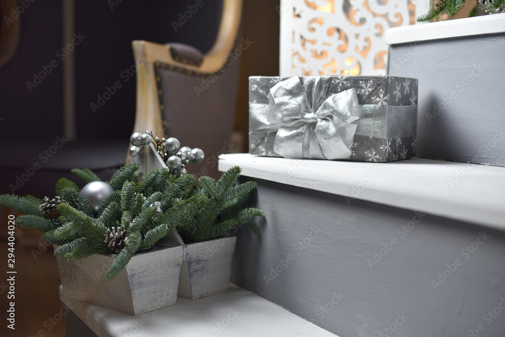 Fototapety, obrazy: Christmas present in silver packaging with a bow, lies on the steps in the house. New year present