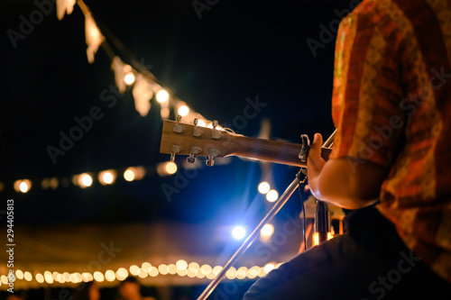 Rear view of the man sitting play acoustic guitar on the outdoor concert with a microphone stand in the front, musical concept. - 294405813