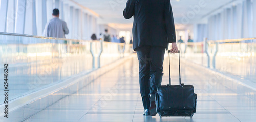 Fototapeta Rear view of unrecognizable formaly dressed businessman walking and wheeling a trolley suitcase at the lobby, talking on a mobile phone. Business travel concept. obraz