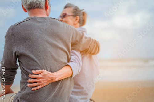 Fotografie, Tablou Retirement couple sitting by the sea, women embrace husbands and look at each other at the beach in the morning, life insurance plan at the retirement concept