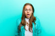 Leinwanddruck Bild - young woman looking very shocked or surprised, staring with open mouth saying wow against blue background