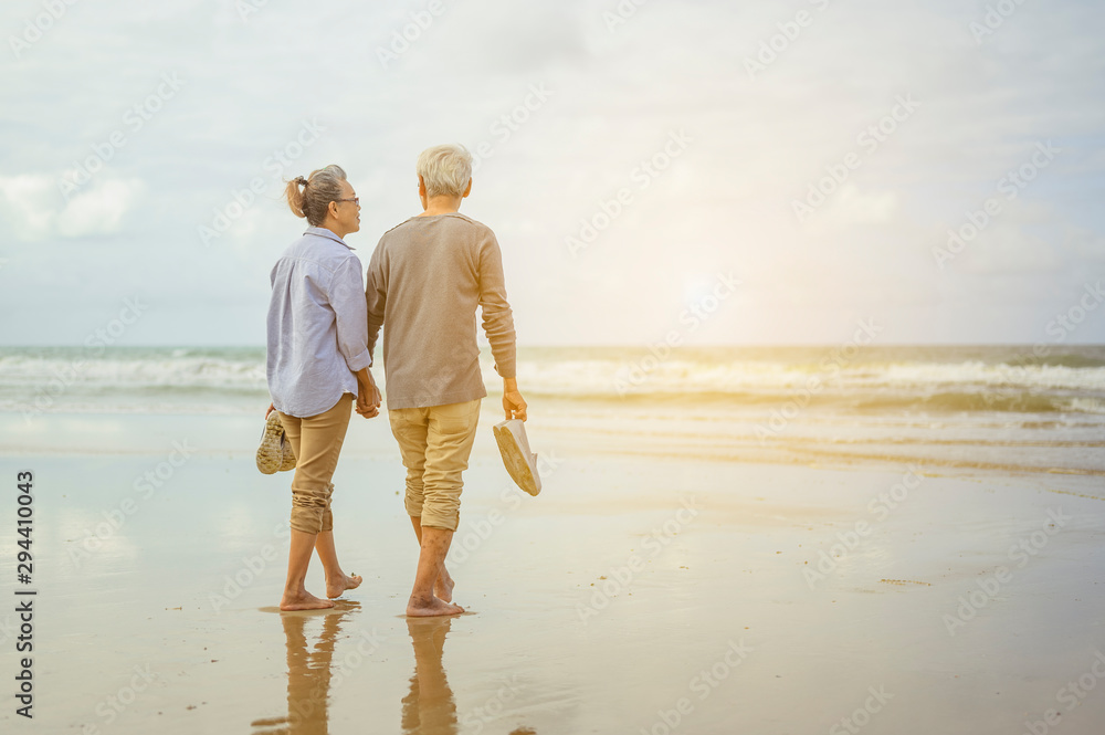 Fototapety, obrazy: Senior couple walking on the beach holding hands at sunrise, plan life insurance at retirement concept.