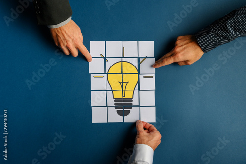 Fotomural Hands of three businessmen assembling a lightbulb drawn on post it papers