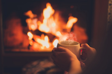 Cup of tea in woman's hands sitting near fireplace