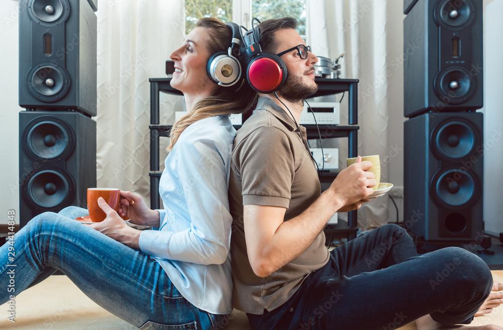 Fototapeta Couple with headphones enjoying music from the Hi-Fi stereo