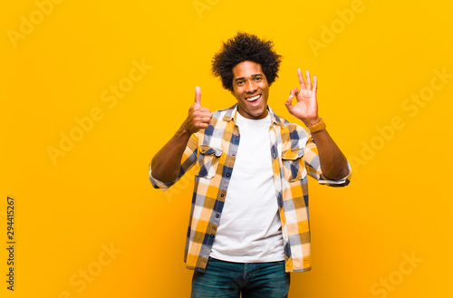 Valokuvatapetti young black man feeling happy, amazed, satisfied and surprised, showing okay and