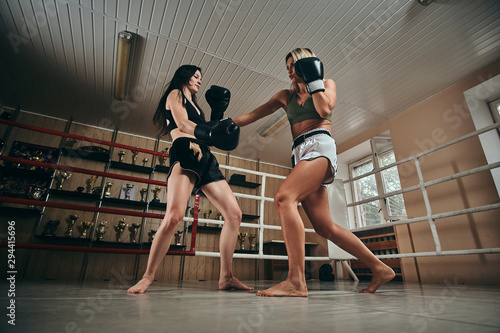 Vászonkép  Boxing coach and her trainee have a sparring on the ring at special gym