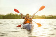 Happy young caucasian couple kayaking on river with sunset in the backgrounds. Having fun in leisure activity. Happy male and female model laughting on the kayak. Sport, relations concept. Colorful.