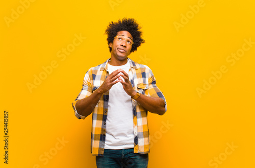 Photo young black man scheming and conspiring, thinking devious tricks and cheats, cun